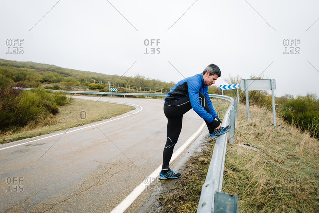 Sporty man lacing winter running shoes and getting ready for outdoor road workout.