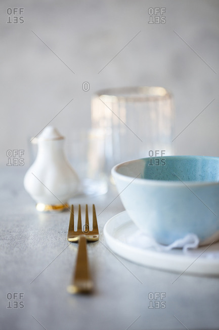 Table setting with blue bowl and gold fork