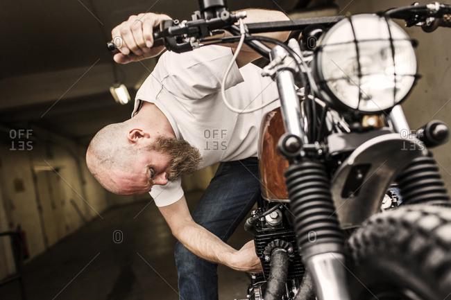 Man repairing motorcycle in workshop