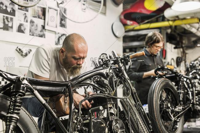 Two men repairing retro motorcycles in workshop