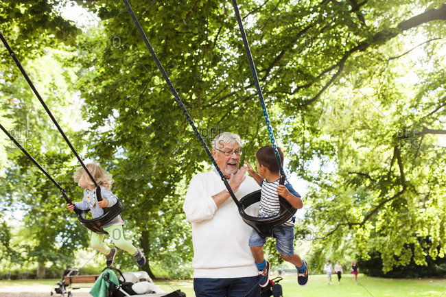 Grandfather swinging grandchildren in playground