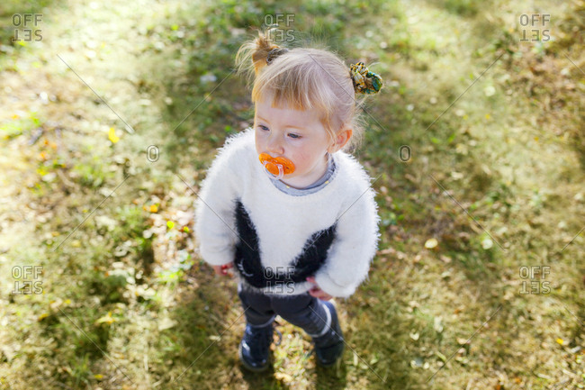 Portrait of girl with pacifier in park