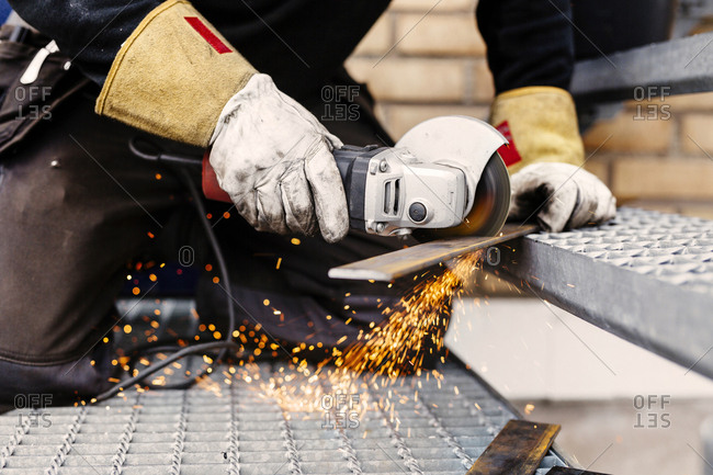 Men cutting metal with grinder