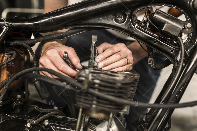 Close up of man repairing retro motorcycle