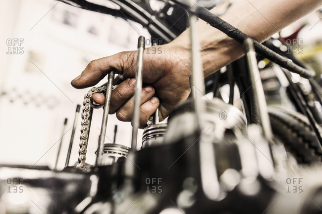 Close up of man holding chain while repairing motorcycle