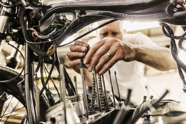 Mature man repairing motorcycle in workshop