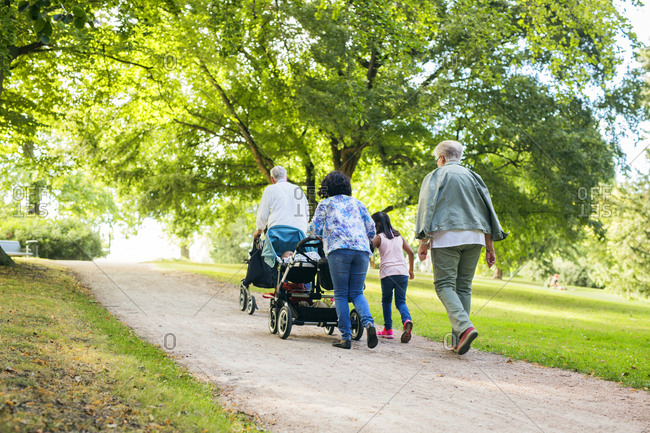 Multi-generation family with children walking in park