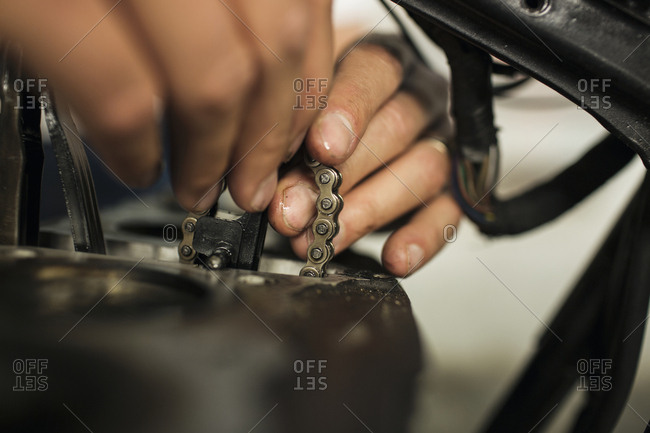Close up of man holding chain during repair of motorcycle