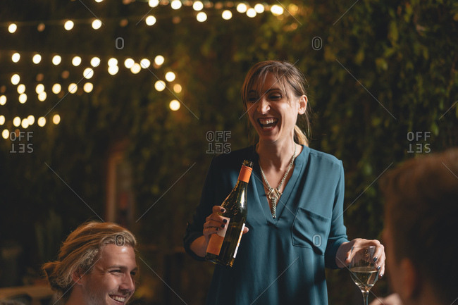 Mid adult woman laughing while holding wine bottle by friend outside