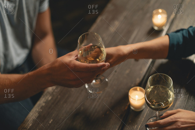 Cropped image of woman passing wineglass to male friend over table at outdoor restaurant