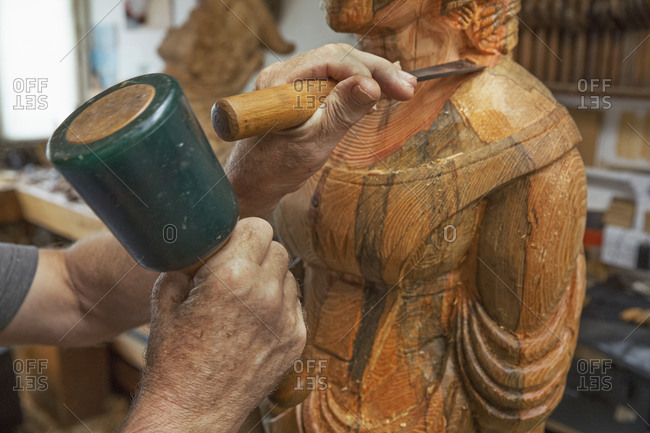A wood carver standing in his workshop, using hand tools, mallet and chisel to shape and create decoration on a work in progress, a wooden female ship's figurehead.