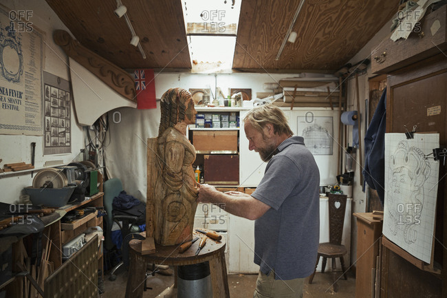 A wood carver standing in his workshop, using hand tools to shape and create decoration on a work in progress, a wooden female ship's figurehead.