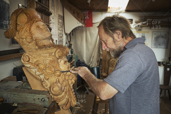 A craftsman, a wood carver working on a wooden female ship's figurehead held in a vice on the workbench of his workshop.