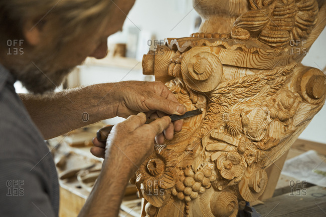 Close up of a craftsman working with a hand tool, using a small woodworking chisel on the wooden decorative features of a ship's figurehead in a workshop.
