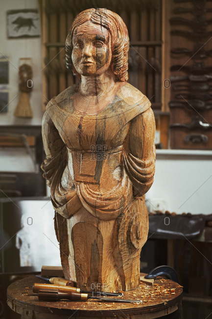 A carved wooden female ship's figurehead on a bench in a workshop with a pattern of wood grain markings,