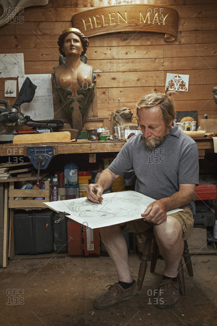 A craftsman, woodworker seated on a stool in a workshop working on a drawing, sketching using charcoal. Surrounded by wooden carved and painted female ship's figureheads.