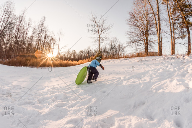 Young boy hauling a sled to the top of a hill