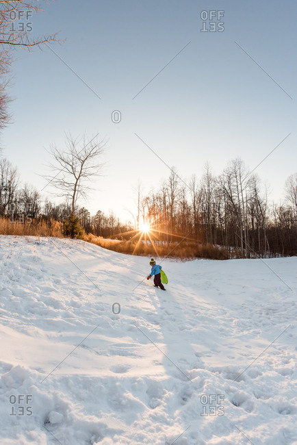 Young boy climbing a snow covered hill with a sled