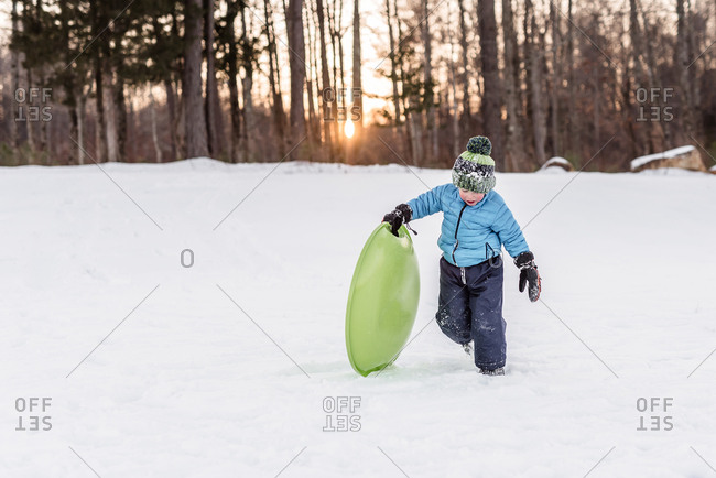Young boy playing with a sled in the snow