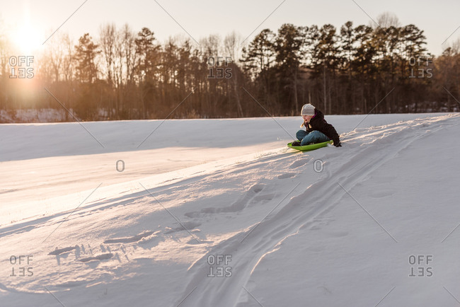 Girl sledding down a snow covered hill