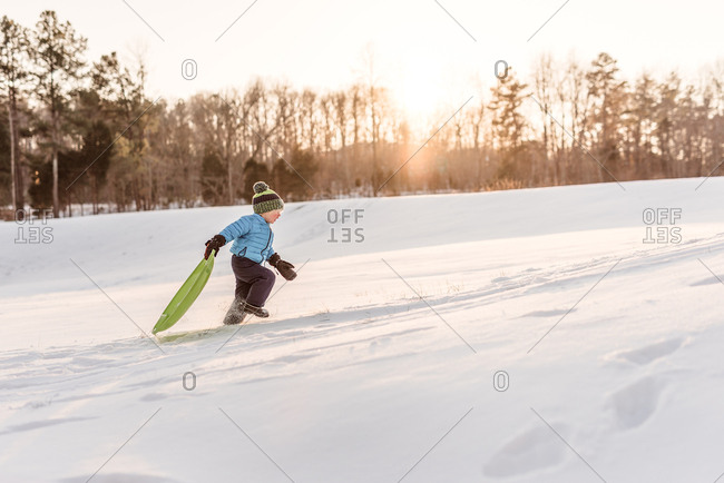 Young boy running up a hill with a sled