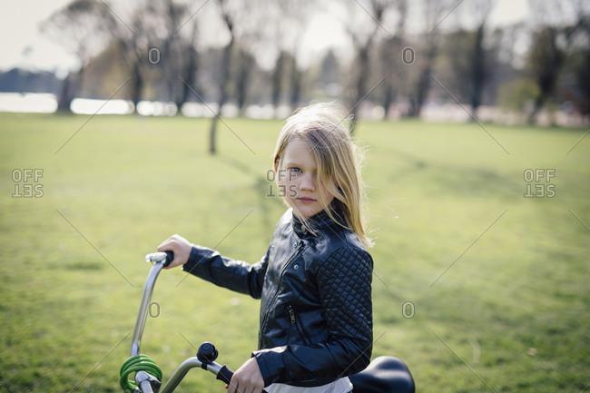 Girl outdoors with a bike in a park. In Lauttasaari, Helsinki, Finland