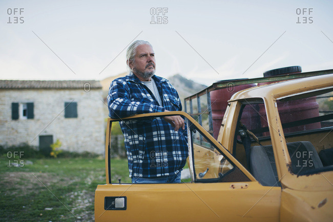 Man with gray hair and beard standing in door opening of old yellow pick-up truck.