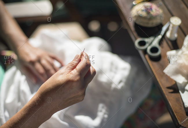 Hand of woman sewing with needle and thread. High angle view.