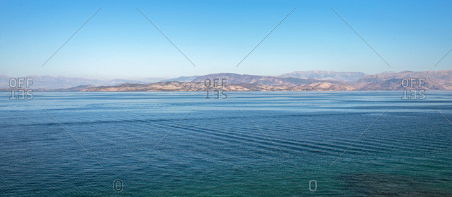 Sea and mountains under clear blue sky.