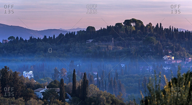 Houses in misty hills lit by morning sun. Corfu, Greece.