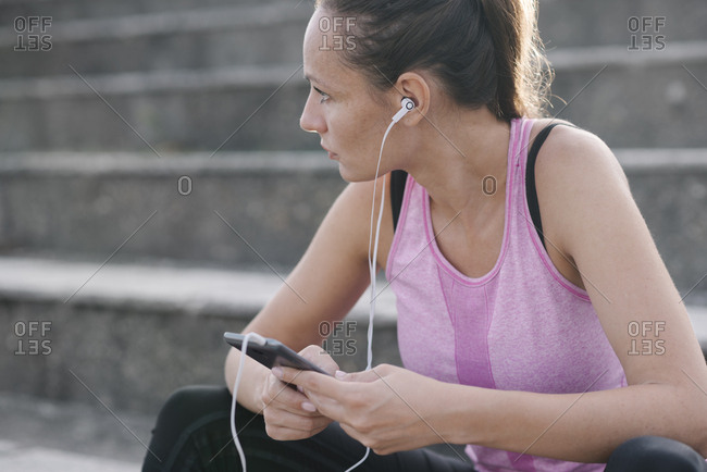 Woman in sport clothing holding smart phone and listening to music.
