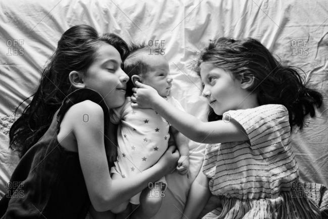 Baby lying between older sisters