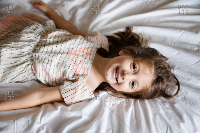 Smiling girl lying down on bed