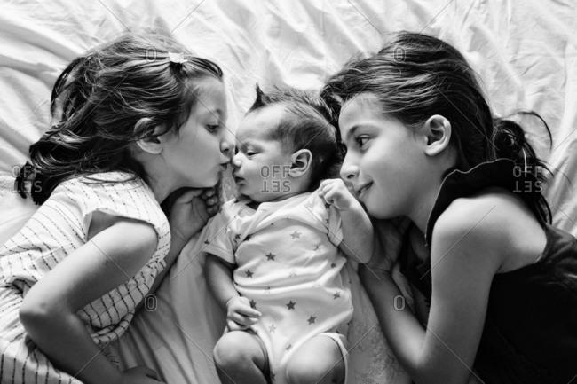 Girl kissing baby lying between older sisters
