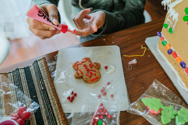 Boy using icing to decorate gingerbread cookie