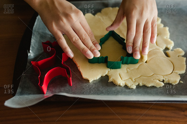 Boy using a tree-shaped cookie cutter to make sugar cookies