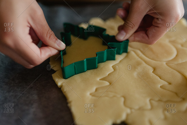 Boy using a cookie cutter shaped like a Christmas tree to make sugar cookies
