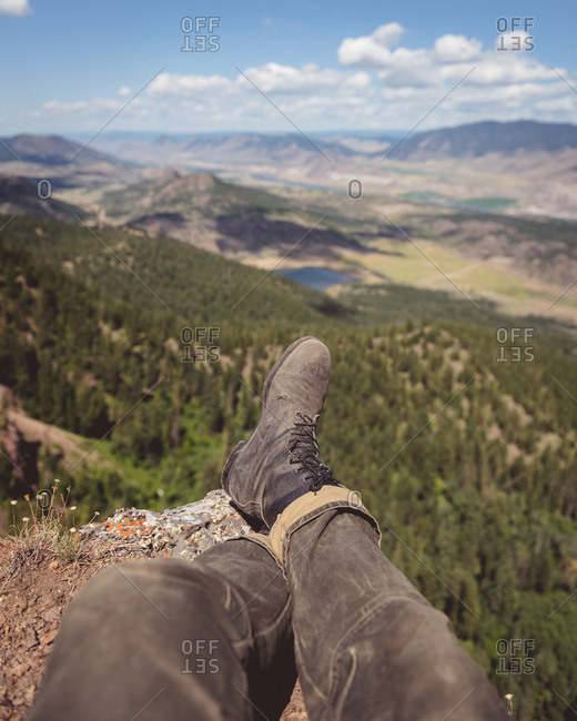 Man's feet sitting on cliff overlooking landscape in Kamloops, British Columbia