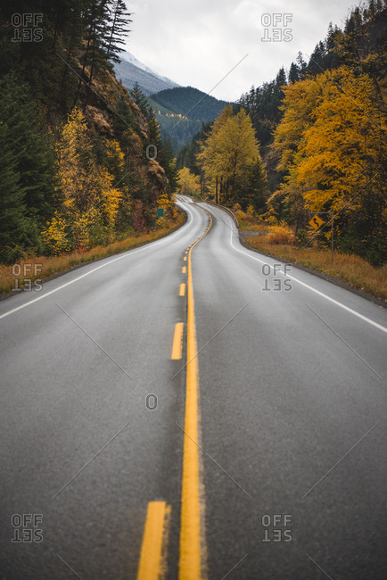 Two lane highway surrounded by autumn trees, British Columbia, Canada