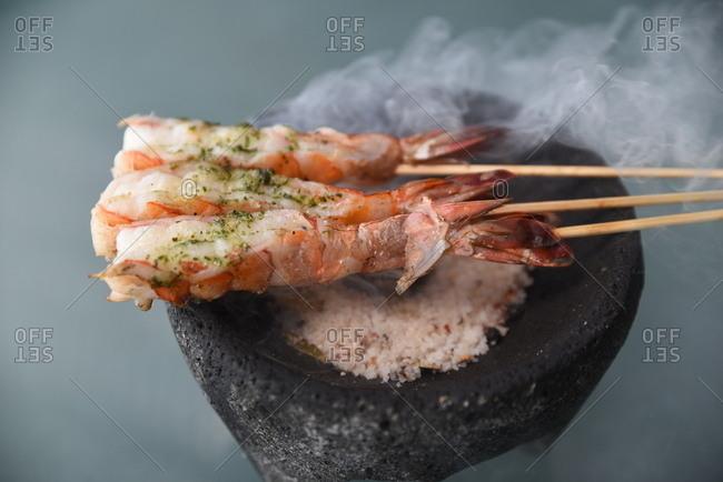 Three smoking shrimp skewers