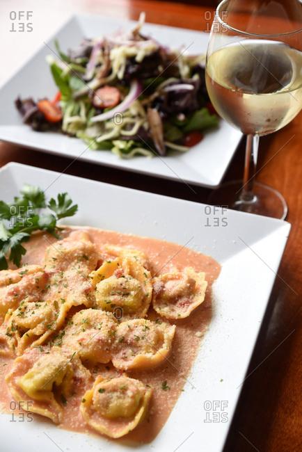Ravioli dish served with wine