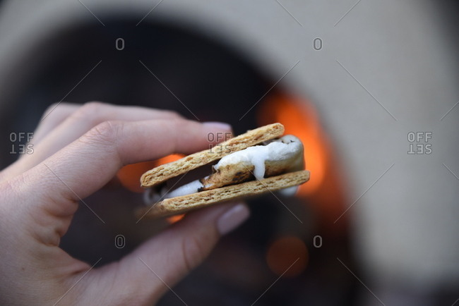Close up of a woman's hand holding a s'more