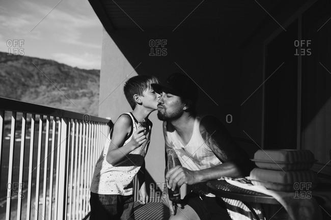 Boy kissing dad on cheek