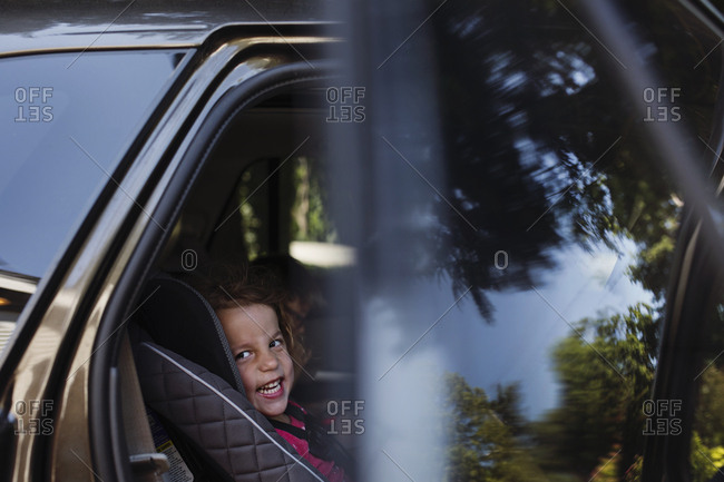 Young child laughing in back seat of open car