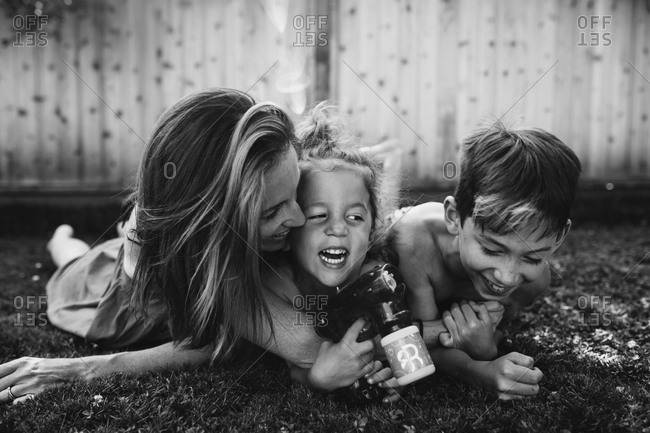 Kids having fun with mom in grass