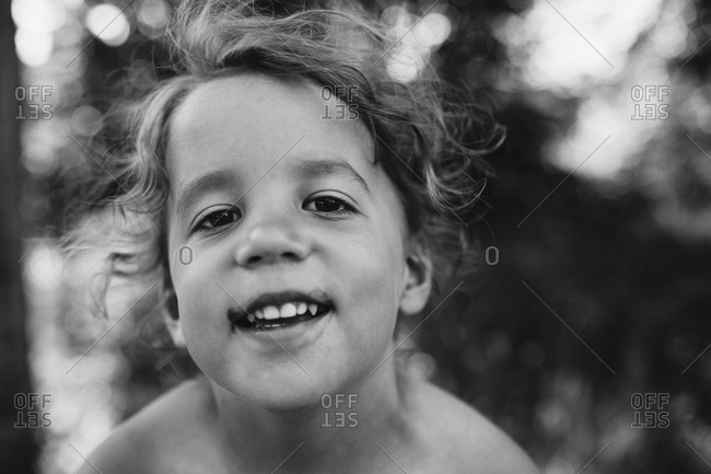 Young boy smiling with flyaway hairs