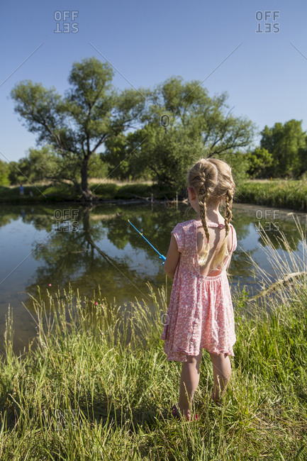 Blonde girl in pink dress fishes in a pond