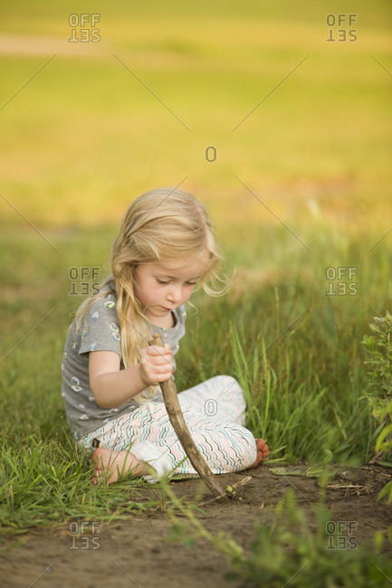 Girl plays outside in the dirt