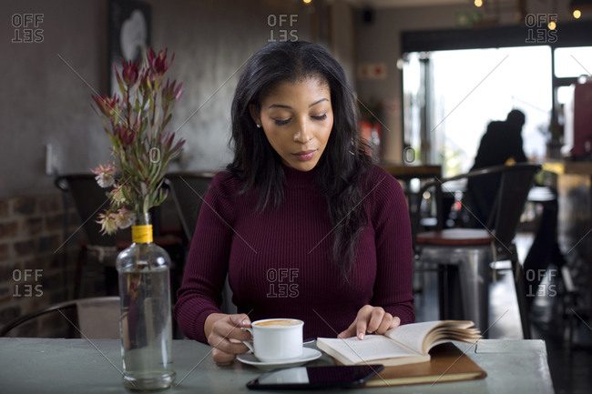 Woman with a cappuccino reading a book