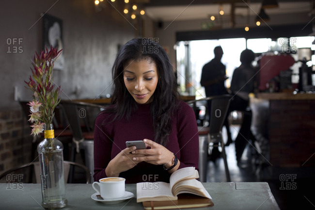 Woman on her phone and reading a book and a coffee shop